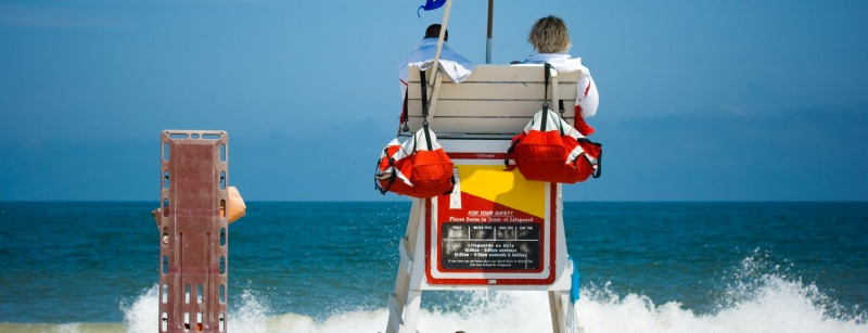Two young men beach lifeguards watch people swimming in the blue ocean with waves crashing on a sandy beach.