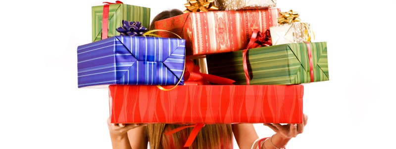 woman holding several christmas gifts covering her face and upper body